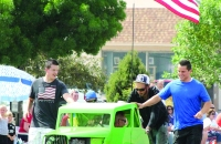 Bystanders push off a car performing tricks in the Fillmore parade.