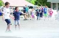Children enjoy water spray from a fire tanker truck during the Fillmore parade.